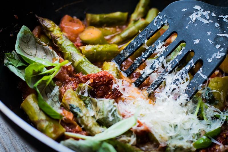 SZPARAGI WPOMIDORACH ZKOZIM SEREM - szybki pomysł naszparagi  Składniki:  pęczek szparagów zilonych  3 pomidory sparzone iobrane zeskóry  pół szklanki wody  3 łyżki sosu sojowego jasnego  szczypta soli  1/2 łyżeczki czarnego pieprzu  sok z1 cytryny  8 suszonych pomidorów pokrojonych wcienkie paski  szczypta soli czosnkowej  pęczek posiekanej zielonej pietruszki  1 rolada zkoziego sera  50 g tartego parmezanu  Przygotowanie:  Szparagi umyj iodkrój twarde końcówki. Pokrój je namniejsze kawałki. Wwoku zagrzej wodę iwrzuć doniej szparagi. Przezchwilę gotuj. Dodaj pomidory pokrojone namniejsze kawałki. Następnie dopraw wszystkimi przyprawami idodaj sos sojowy. Dorzuć suszone pomidory ipodgrzewaj jeszcze chwilę aż zpomidorów zrobi się sos. Przedpodaniem posyp zieloną pietruszką, dodaj kozi ser, posyp parmezanem iskrop sokiem zcytryny.